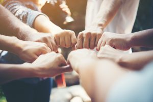 Close up of young people putting their hands together. Team with